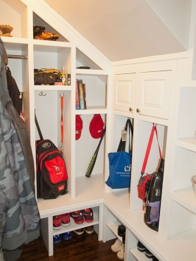 The mudroom, located next to the powder room utilizes unused space under the stairs to provide room for cubbies, hanging space, as well as shelving for shoe storage.
