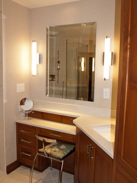The separate vanity area for her includes a make-up vanity, which seamlessly integrates into the custom cabinetry.