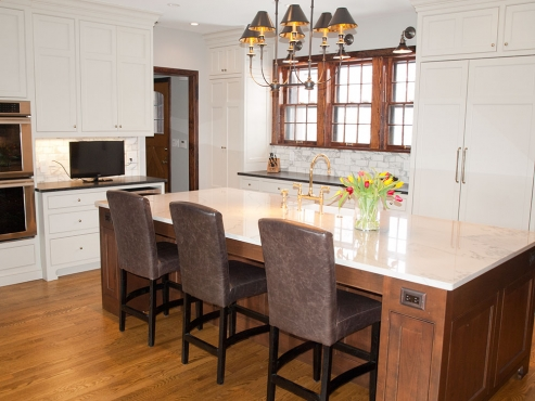 The design called for custom cabinetry, with an oversized, stained island, creating a casual eat-in area, while still maintaining a formal space with the paneled refrigerator and custom 5-piece cabinet doors.