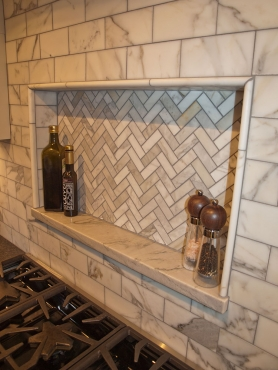 A recessed niche over the cooktop creates a space for oils and spices just an arm's reach away.  A classic subway tile gets a sophisticated update in Calacatta marble, which is accented by a marble herringbone mosaic.