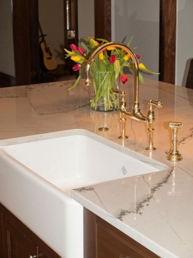 A large Rohl, apron-front sink and polished brass faucet add beautiful detail to the large piece of Calacatta quartzite gracing the oversized island.