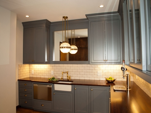The original butler's pantry was updated with new custom-cabinets, hardwood floors, reclaimed wood counters – complete with a bar refrigerator, kegerator, bar sink and dishwasher.
