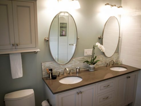 The custom vanity and coordinating wall cabinet maximize storage and reflect the traditional details of the home.