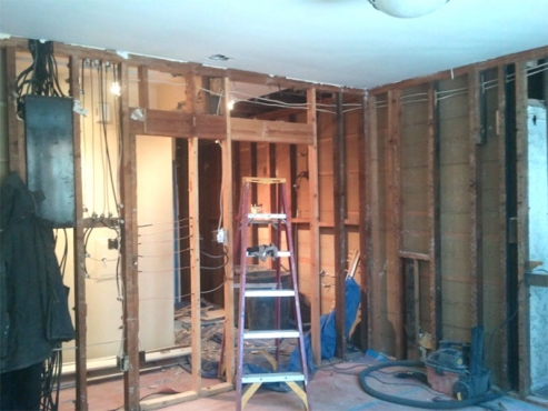 Load-bearing wall and electrical service panel to be removed to make way for double ovens, cabinets and counter tops.