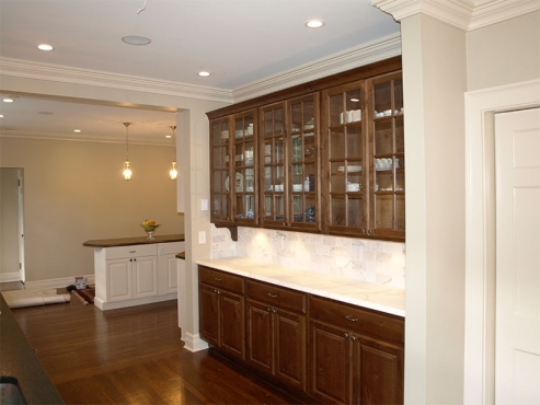 Butler's pantry with honed marble countertops and custom marble backsplash. Under cabinet lighting accentuates this timeless white marble.