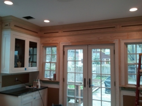 Notice the custom multi-stage woodwork being installed above cabinets. Once painted, a seamless transition between ceiling and cabinets will be achieved.