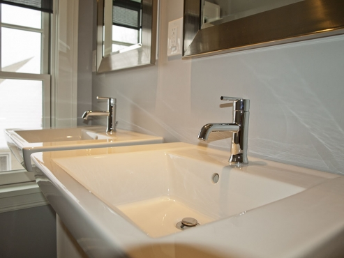 New white American Standard Boulevard pedestal sinks with chrome, one handle Delta faucets create a contemporary feel in an otherwise traditional Shaker Heights home.