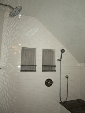 The shower features his and hers niches, a large chrome Jaclo showerhead and handheld shower.