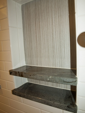 The custom shower niches can hold large shampoo bottles with additional shelf space for soap.  The custom niche shelves match the Silver Cloud stone used on the shower bench and shower threshold.