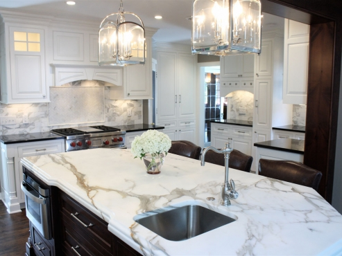 The soft white cabinetry, along with the honed Calacatta Gold island top and subway tile backsplash create a bright and airy atmosphere. The dark hardwood floors, wood-wrapped ceiling beam and island cabinets bring balance and warmth to the space.